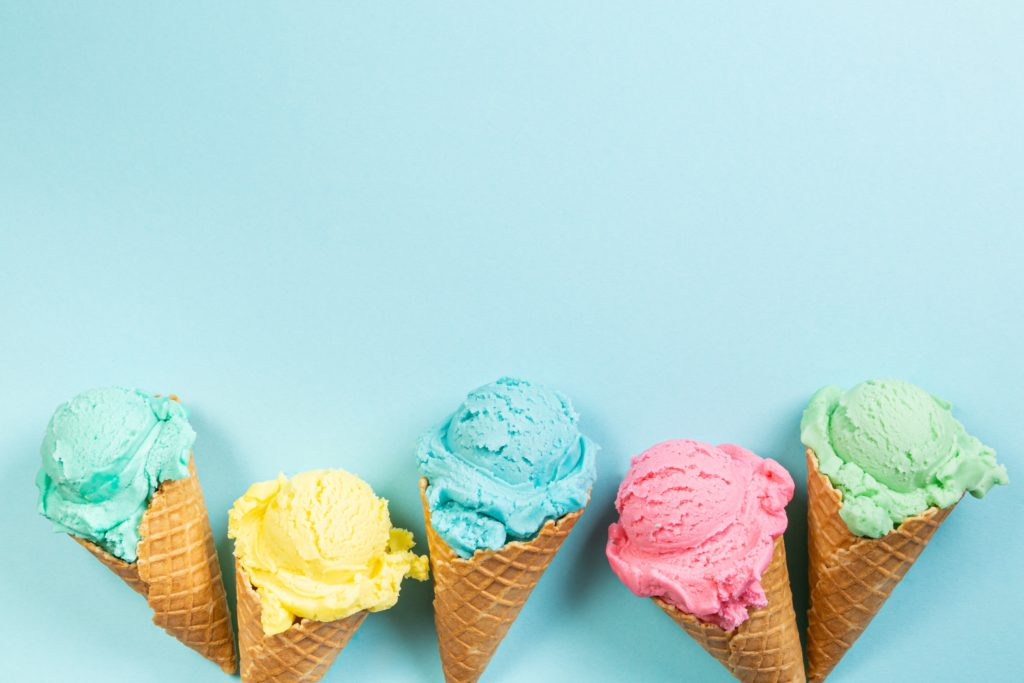 Pastel ice cream in waffle cones, bright background, copy space